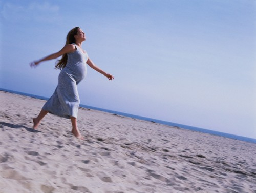 Pregnant Woman Strolling Along the Beach